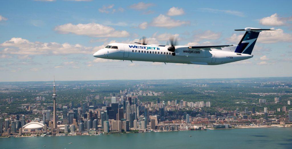 WestJet airplane flying above Toronto